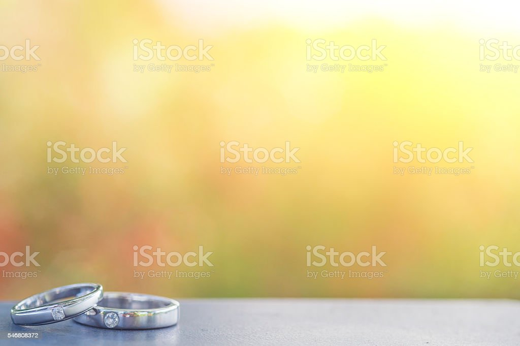 Wedding rings on steel with colorful bokeh stock photo