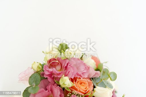 istock wedding rings on the bouquet with flowers roses on a white background with copy space. minimal concept. mockup 1155479311