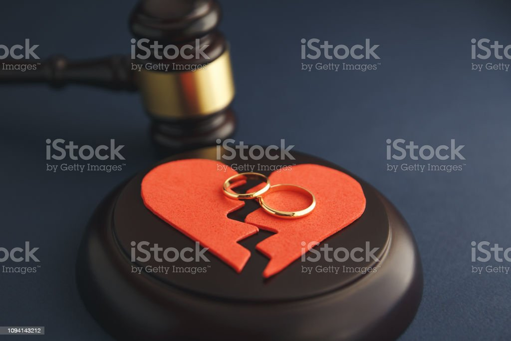 Wedding rings on the figure of a broken heart from a tree, hammer of a judge on a wooden background. Divorce Wedding rings on the figure of a broken heart from a tree, hammer of a judge on a wooden background. Divorce proceedings Broken Stock Photo