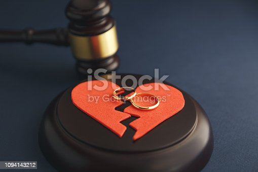 istock Wedding rings on the figure of a broken heart from a tree, hammer of a judge on a wooden background. Divorce 1094143212