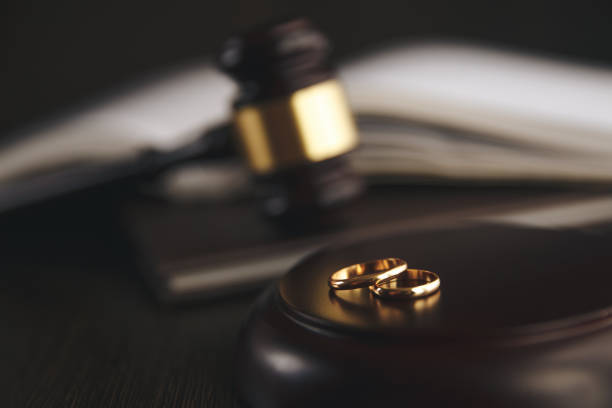 wedding rings on the figure of a broken heart from a tree, hammer of a judge on a wooden background. divorce proceedings - divorzio foto e immagini stock
