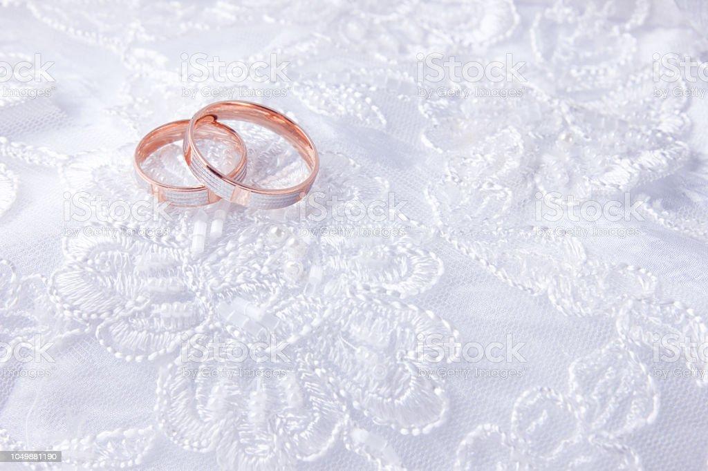 Wedding Rings On Wedding Card On A White Wedding Dress Stock Photo