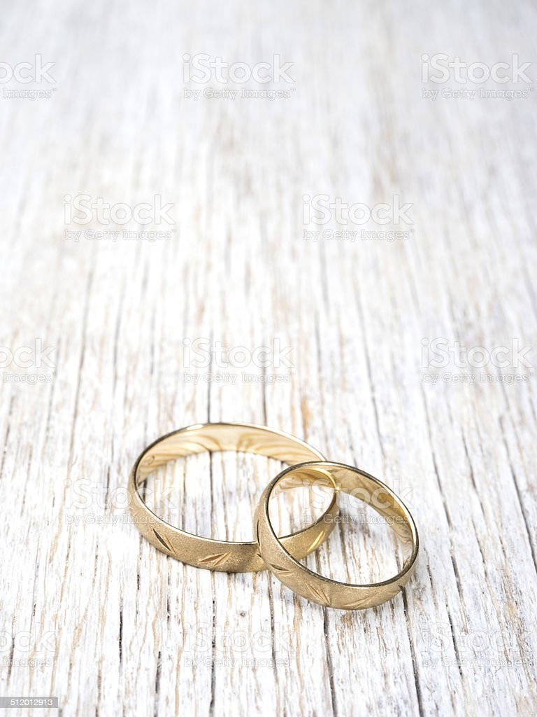 Wedding rings on wooden background stock photo