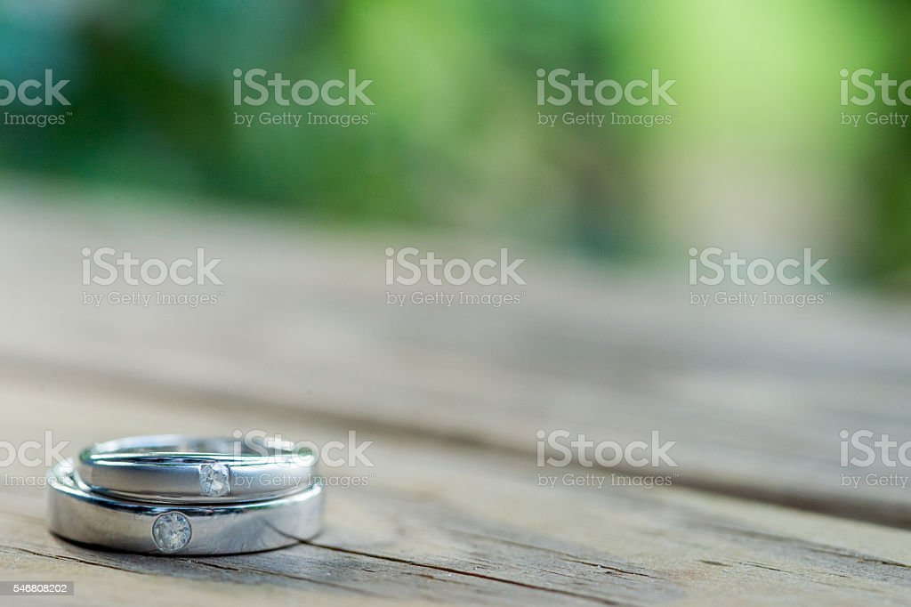 Wedding rings  on  wooden table with bokeh tree background. stock photo