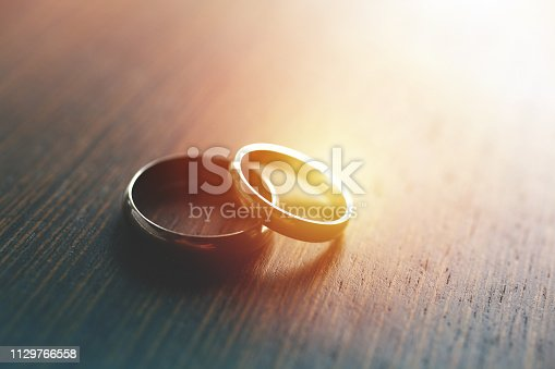 Close-up of wedding rings on table with sunlight.