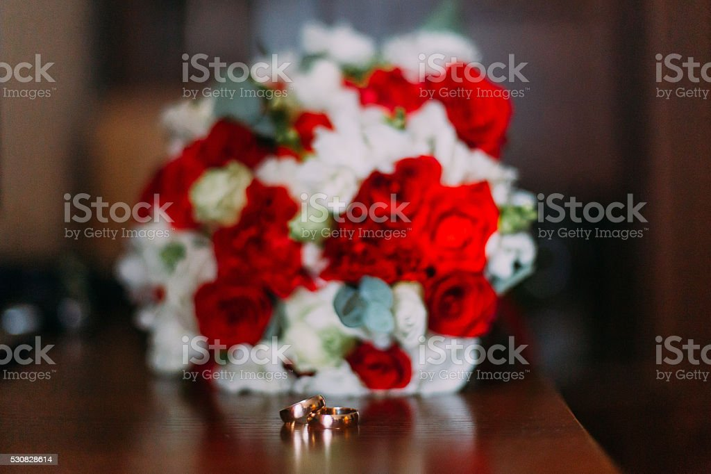 Wedding rings with boutonniere on wooden background in rustic style stock photo