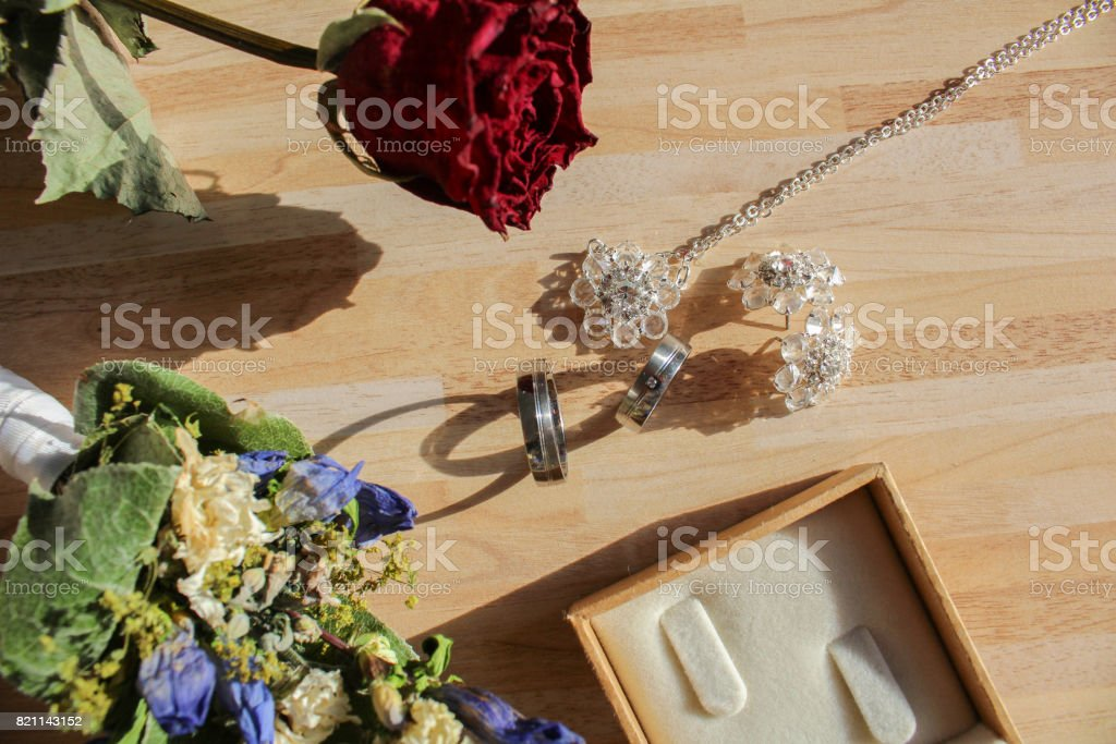 Wedding rings with dry flower and box on wooden background stock photo