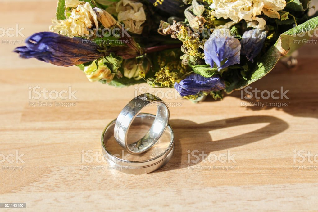 Wedding rings with dry flower on wooden background stock photo