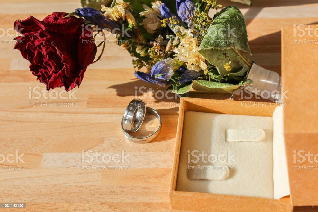 Wedding rings with dry rose and flower and box on wooden background stock photo
