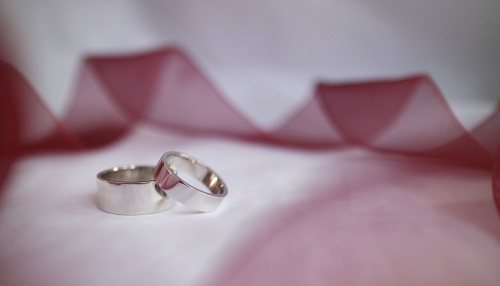 155315629 istock photo Wedding rings with red ribbon 1259738607