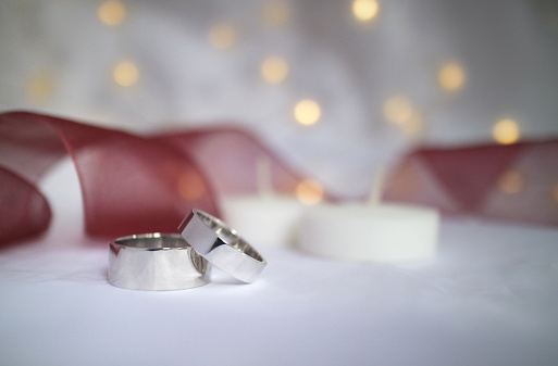 155315629 istock photo Wedding rings with white candel , red ribbon and lamp 1259738601