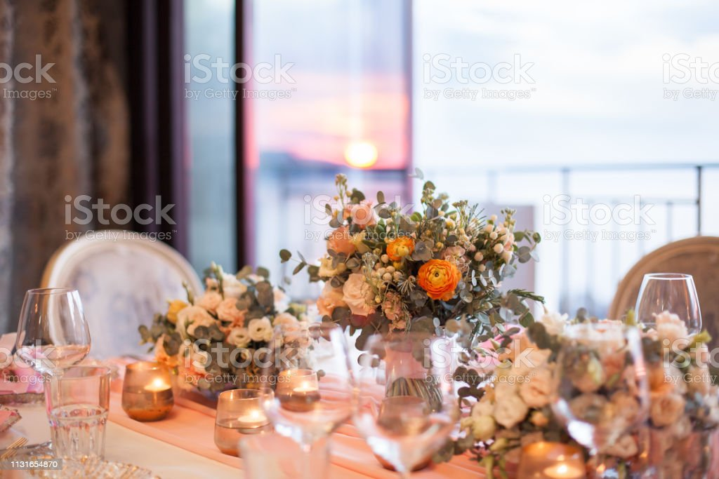 Wedding Romantic Dinner At Sunset By Sea Restaurant After Ceremony Beautiful Flowers Decorations Of Table With Dishes Wineglasses Of Ice Champagne Candles Brides Orange And Pink Bouquet Stock Photo Download Image