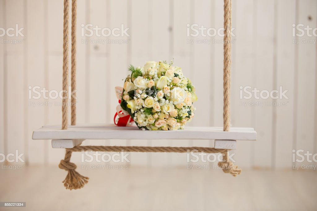 wedding rose bouquet of bride on wooden swing with rope stock photo