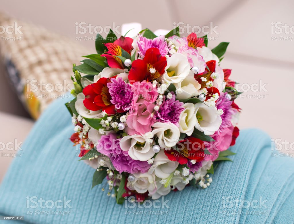 wedding saturate bouquet of different flowers of bride on sofa stock photo