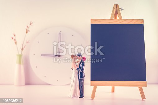 Wedding schedule / wedding plan, planner concept : Miniature figurine couple wedding doll, bride & bridegroom, chalkboard for noting ceremony time and welcome guest to the propitious, felicitous event