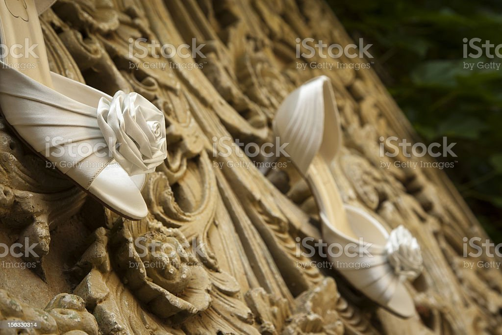 wedding shoes hanging on a stone wall royalty-free stock photo