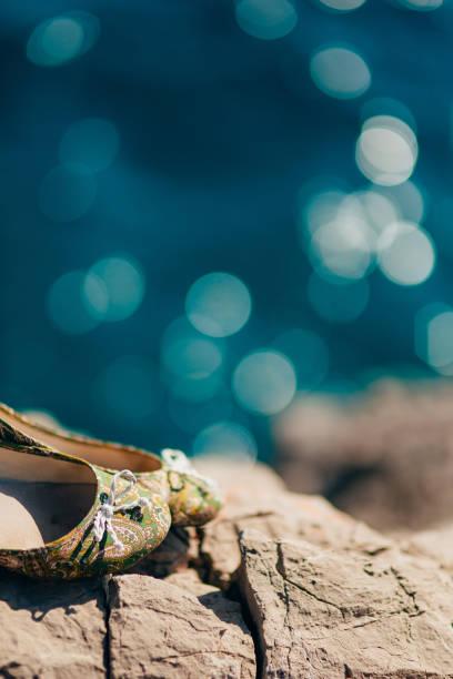 hochzeitsschuhe auf den felsen am meer - goldhochzeitsschuhe stock-fotos und bilder