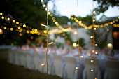 A string of fairy lights hanging in-between trees photographed shining at night with image focus technique focus on the foreground bokeh background and dark Franschhoek Cape Winelands South Africa
