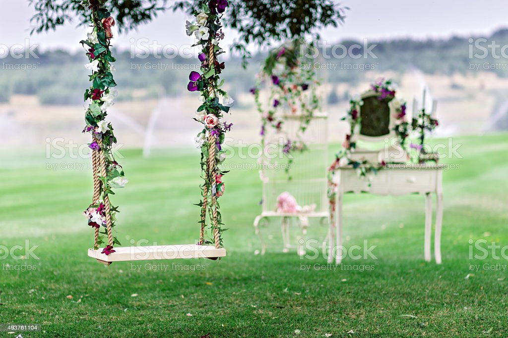 Wedding swing decorated with flowers stock photo