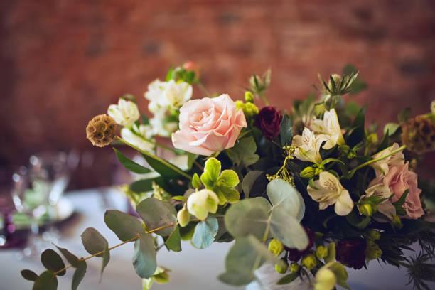 bruiloft tabel versierd met bloemen - bloemstuk stockfoto's en -beelden