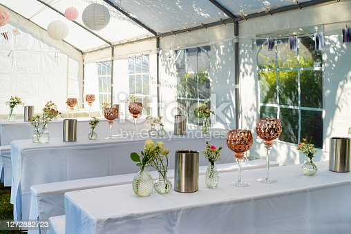 Wedding table setting decorated with fresh flowers in a vase, champagne coolers, and decorative glasses. Banquet table for guests outdoors with a view of green nature.