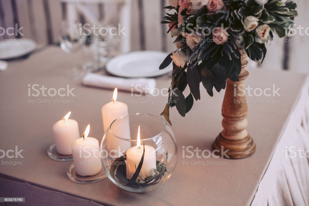 Wedding Table With A Bouquet Of Flowers In A Vase And Lighted