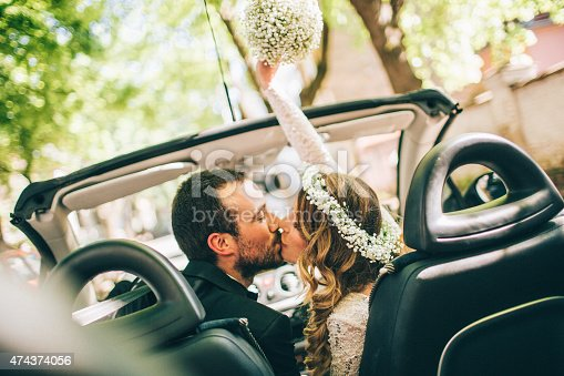 Photo of just married couple. They are kissing in the car.