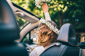 Photo of bride sitting in the car. She has corolla at the head and holding bouquet.