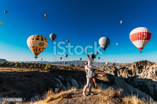 istock Wedding travel. Honeymoon trip. Couple in love among balloons. A guy proposes to a girl. Couple in love in Cappadocia. Couple in Turkey.  Man and woman traveling. Flying on balloons. Tourists 1142802668