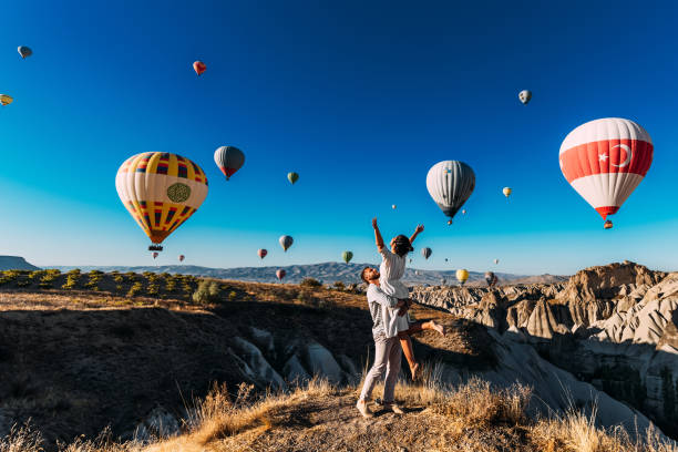 wedding travel. honeymoon trip. couple in love among balloons. a guy proposes to a girl. couple in love in cappadocia. couple in turkey.  man and woman traveling. flying on balloons. tourists - destination stock pictures, royalty-free photos & images