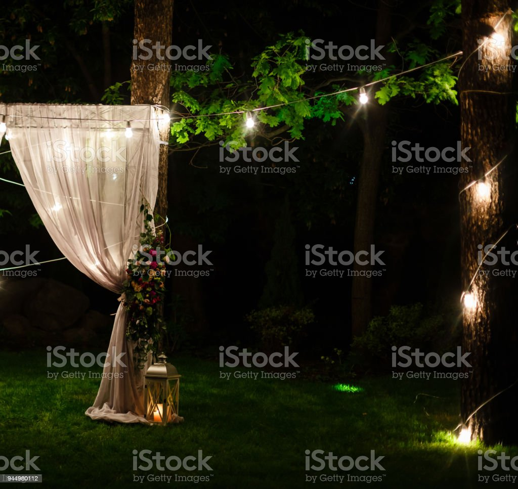 Wedding twilight ceremony decoration made of hanging on a tree golden lanterns and lamps and standing on the grass fired candles with the carpet in the middle stock photo