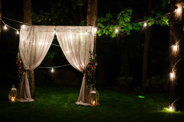 dämmerung zeremonie dekoration an einem baum hängenden goldenen hochzeit laternen und lampen und stehen auf dem rasen feuerte kerzen mit dem teppich in der mitte - grüne wald hochzeiten stock-fotos und bilder