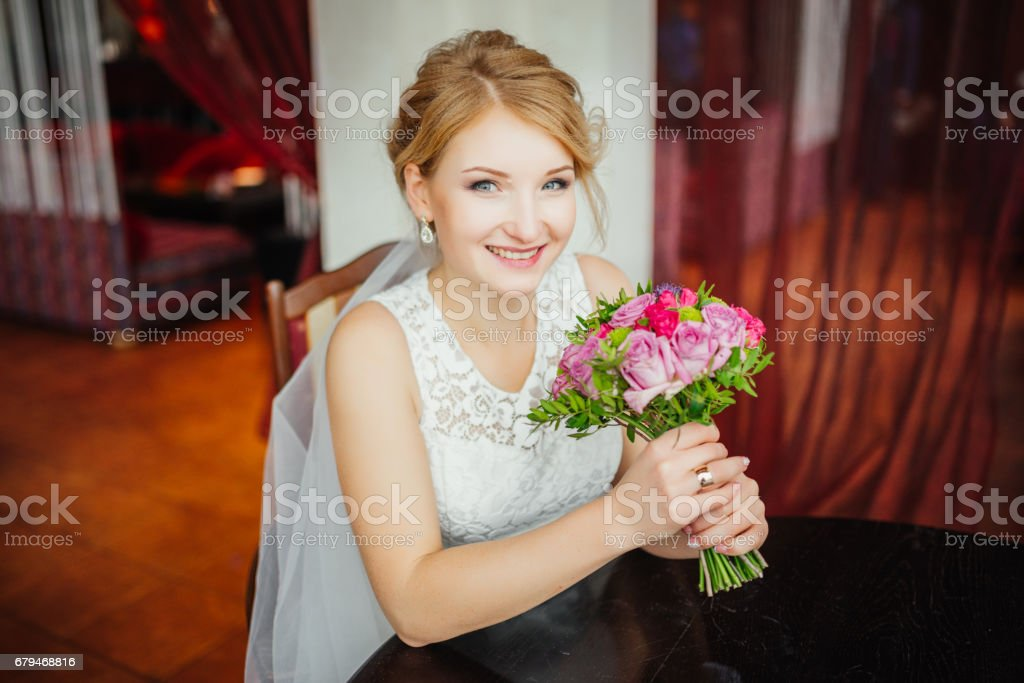 Wedding. Wedding day. Beauty bride in bridal gown with bouquet and lace veil indoors. Beautiful model girl in a white wedding dress. Female portrait of cute lady. Woman with hairstyle royalty-free stock photo