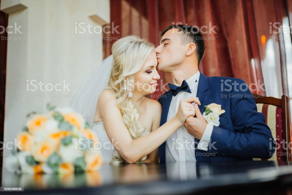 Wedding. Wedding day. Groom kisses the bride on the forehead after wedding ceremony. Bridal bouquet royalty-free stock photo