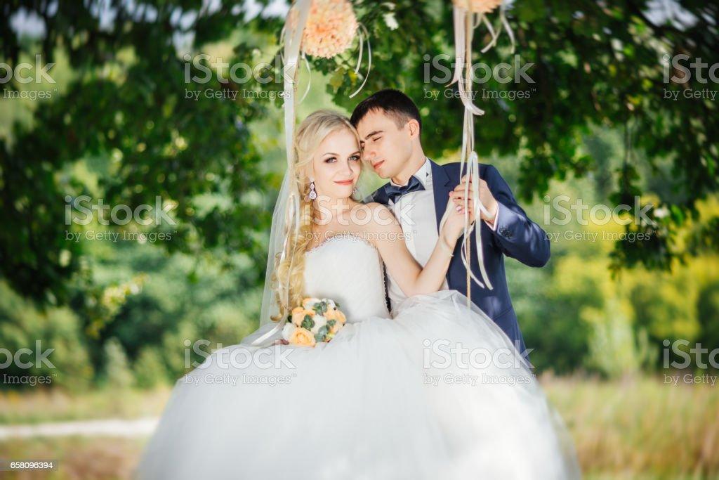 Wedding. Wedding day. Happy beautiful family couple. Groom hugs bride near the swing after wedding ceremony. royalty-free stock photo