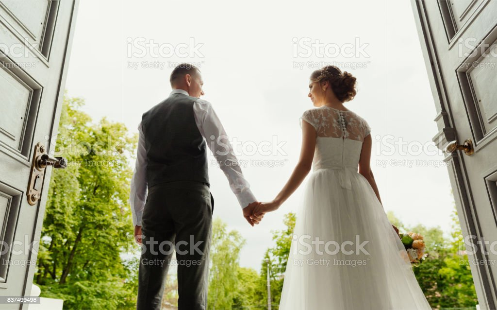 Wedding. Wedding day. Wedding couple. Beautiful couple, bride and groom look at each other and hold hands, against the background of the exit from the cathedral (large tall doors) stock photo