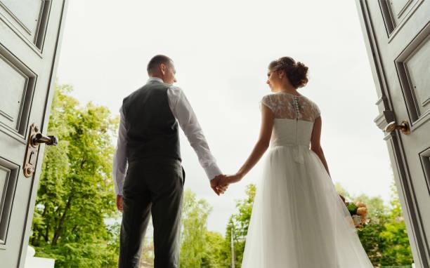 bröllop. bröllopsdag. bröllopsparet. vackert par, bruden och brudgummen ser på varandra och hålla varandra i handen, mot bakgrund av avfarten från katedralen (stora höga dörrar) - nygift bildbanksfoton och bilder