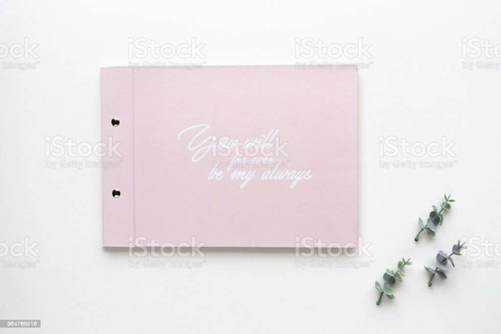 Wedding wish book and oregano branches on white marble  Top view. royalty-free stock photo