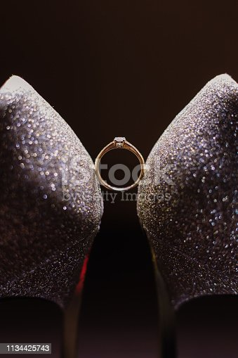 Wedding women's shoes with a wedding ring illuminated by photo light