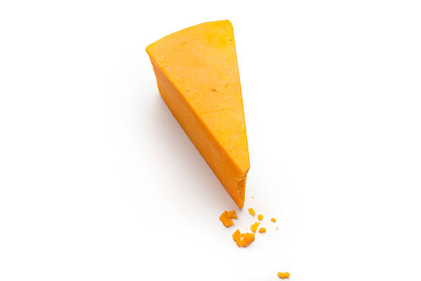 Wedge of Cheddar Cheese a wedge and some crumbs of cheddar cheese on a white studio background. cheddar cheese stock pictures, royalty-free photos & images