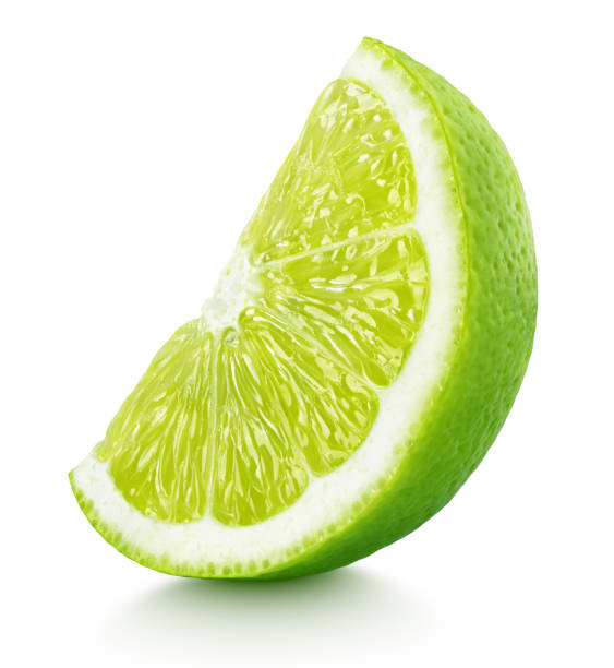 wedge of green lime citrus fruit isolated on white Ripe slice of green lime citrus fruit stand isolated on white background with clipping path lime stock pictures, royalty-free photos & images