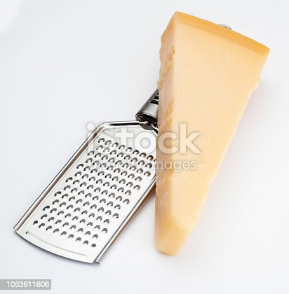 Wedge of Parmesan cheese or grana with grater. Isolated on white background.
