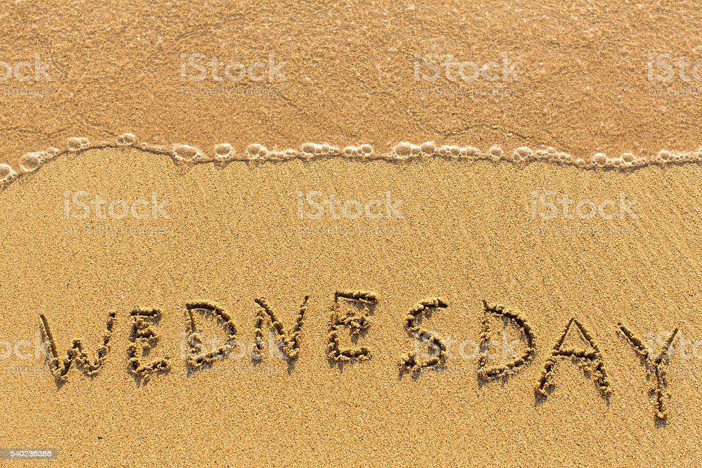 Wednesday - drawn on the sand beach stock photo