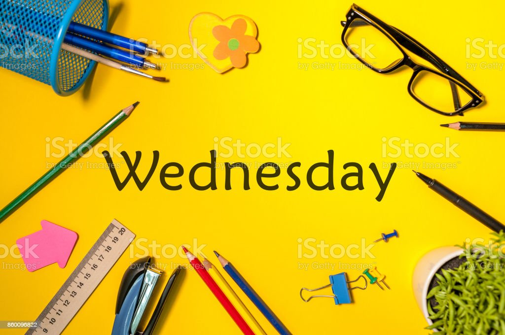 Wednesday. Office supplies or student outfit on yellow table. Business creative consept, top view stock photo