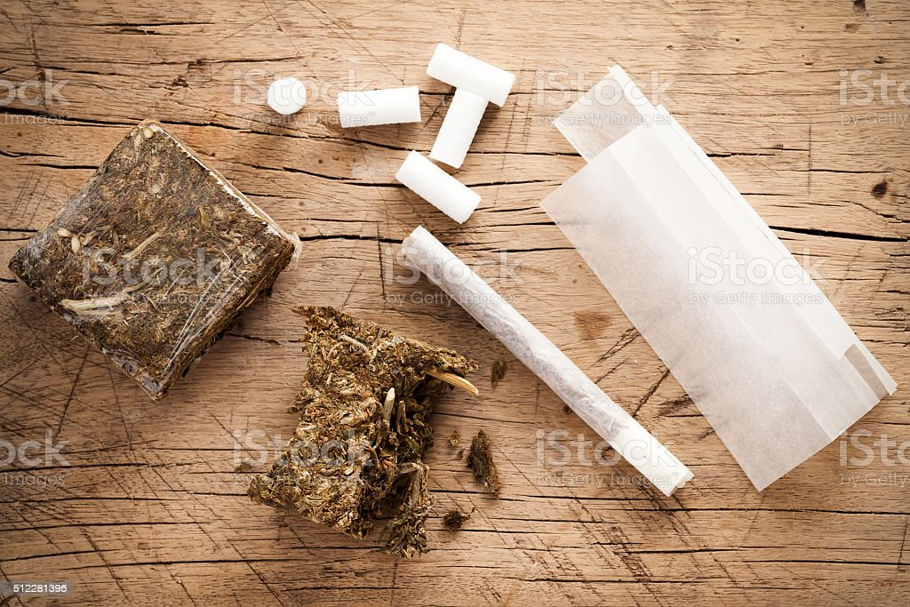 weed marijuana hashish roll wood background stock photo