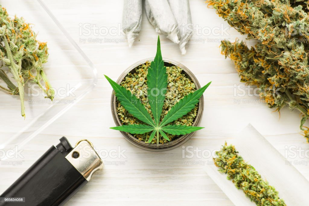 weed on a white wooden background, grinder with crushed Joint an use THC and CBD - Royalty-free Addiction Stock Photo