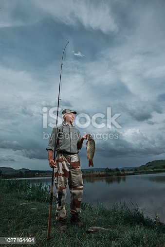 senior man holding fish capture and looking away near his fishing rod.
