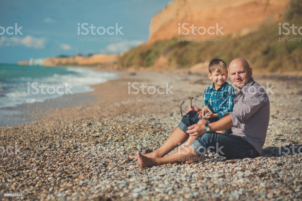 Weekend at the beach Dad and son sitting on the beach and looking at each other. A beach Stone sea foam pedigree royalty-free stock photo