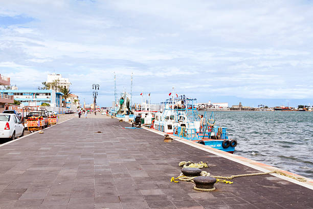 Weekend at Veracruz Port Veracruz, Mexico - November 23, 2013: The malecon at Veracruz port on a saturday morning, with fishermen at right doing maintenance to their vessel. veracruz stock pictures, royalty-free photos & images