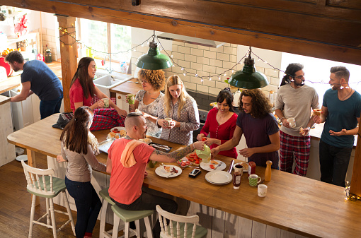 A group of friends are preparing breakfast in the kitchen, they are eating bacon sandwiches and chatting happily amongst themselves. It looks like they are on a weekend away vacation.